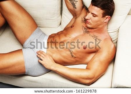 Man with beautiful muscular tattooed torso in underwear lying on sofa - stock photo