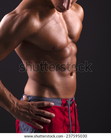 Man with beautiful torso on black background - stock photo