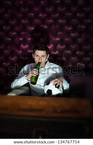 Man with beer and football ball watching a game in TV - stock photo