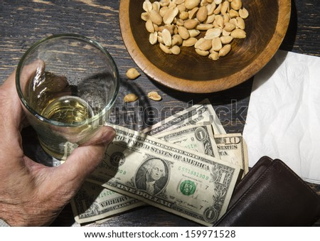 man with beer leaving tip on bar - stock photo