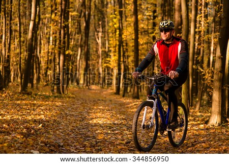 Man with bicycle riding country roadat afternoon