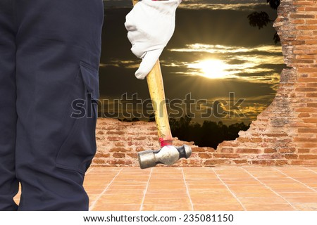 man with big hammer against wall and sun rise - stock photo