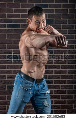 Man with big muscles punches ahead brick wall background.