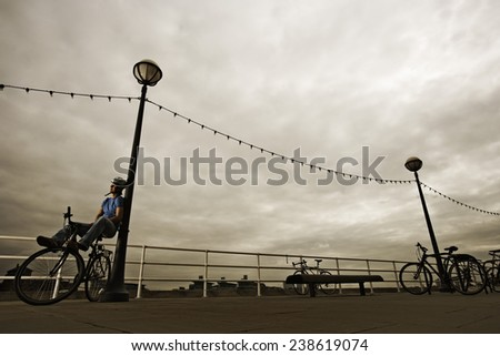 Man with Bike Leaning at Lamppost - stock photo