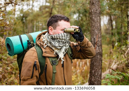 Man with binoculars at a forest. - stock photo