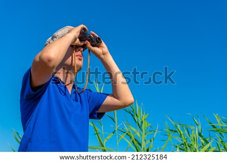 man with binoculars examines bird in the sky - stock photo
