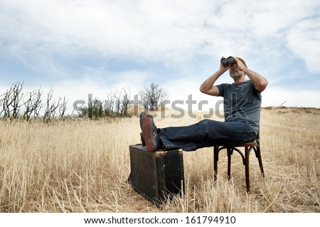 Man with binoculars in a field sitting on chair - stock photo