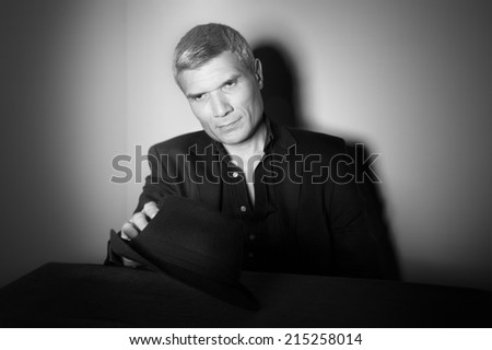 Man with  black hat at the age of forty-six years old holding his hat in his hand and looks at it on the background of a rough wall with texture - stock photo