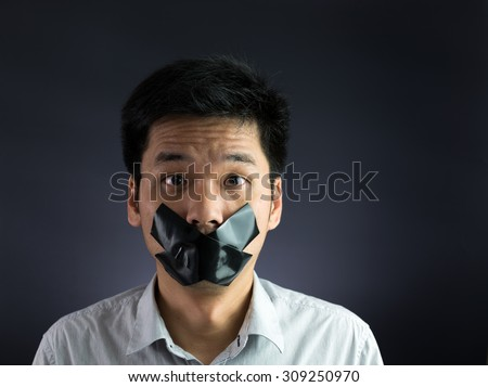 Man with black masking tape over his mouth on black background - stock photo