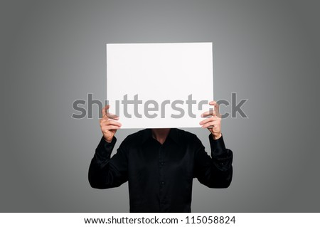 man with black shirt holding blank white board on gray background