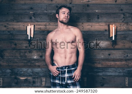 Man with blonde hair and bare chest wearing blue flannel pants. Standing against wooden wall inside wooden cabin. - stock photo