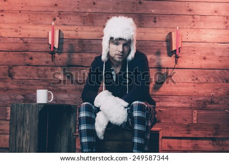 Man with blonde hair, beard and white hat wearing winter sleepwear. Sitting on wooden box inside cabin. - stock photo