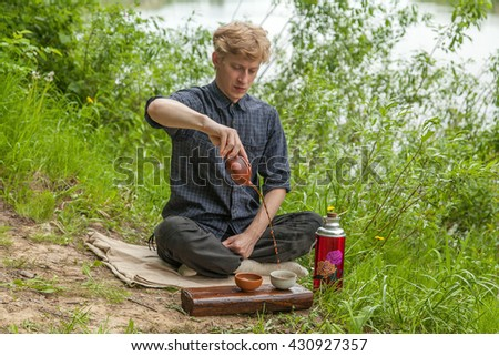 Man with blonde hair making chinese tea at the bank of the river
