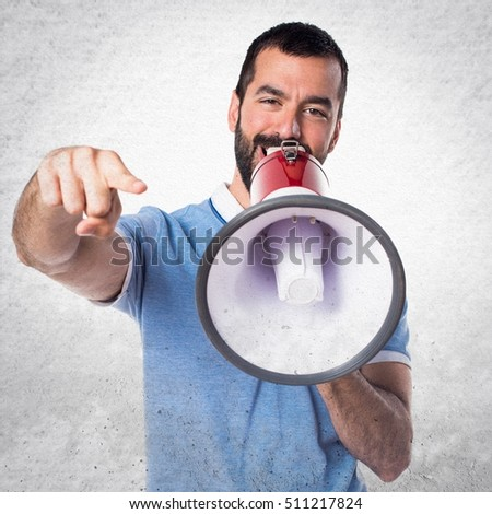 Man with blue shirt shouting by megaphone on textured background