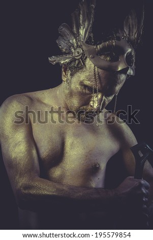 Man with body painted gold feather mask and steel sword - stock photo
