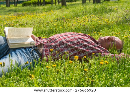 Man with book on a meadow - stock photo
