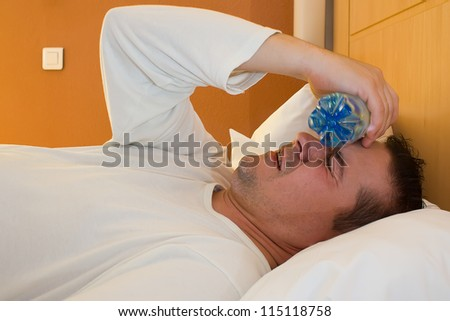 man with bottle and flu and he has a temperature - stock photo