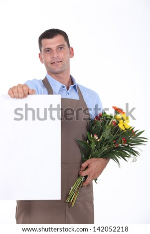 Man with bouquet of flowers and poster - stock photo