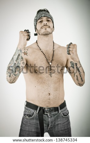 man with brass knuckles in grunge background - stock photo