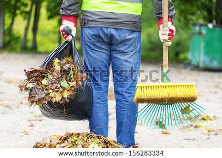 Man with brush and rake collects leaves - stock photo