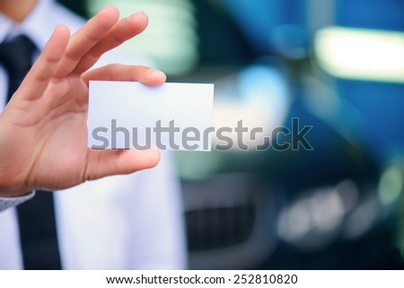 Man with business card. Closeup of a copy space business card in hands of car salesman standing against a luxury car - stock photo