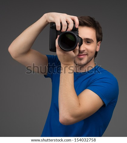 Man with camera. Cheerful young man holding camera in his hands and focusing at you while isolated on grey