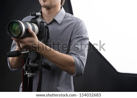 Man with camera. Cropped image of young man holding camera in his hands while standing in studio
