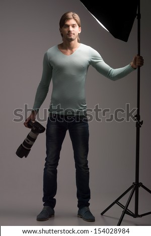 Man with camera. Full length of confident young man holding camera in his hands and looking at you - stock photo