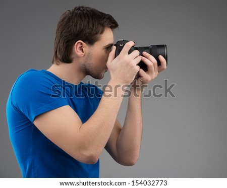 Man with camera. Side view of confident young man holding camera in his hands and focusing while isolated on grey