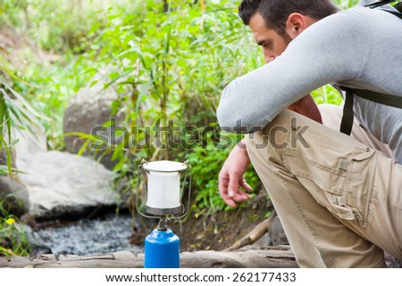 man with camping gas in nature