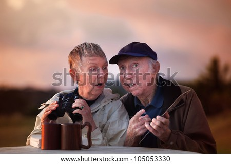Man with card talks to woman holding binoculars - stock photo
