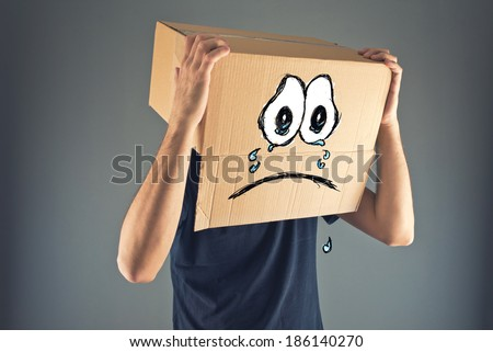 Man with cardboard box on his head and sad crying emoticon face expression. Concept of sadness and depression. - stock photo