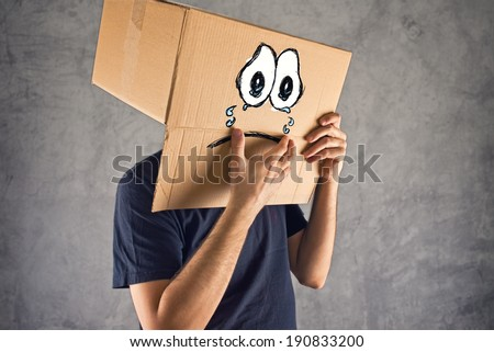 Man with cardboard box on his head and sad crying face expression. Concept of sadness and depression. - stock photo