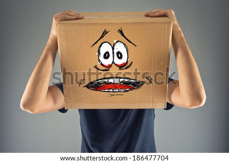 Man with cardboard box on his head and terrified emoticon face look sketched. terrified; frozen; scared man. - stock photo