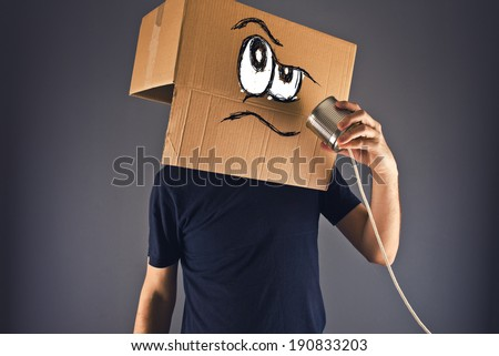 Man with cardboard box on his head using tin can telephone for conversation. Angry face expression.