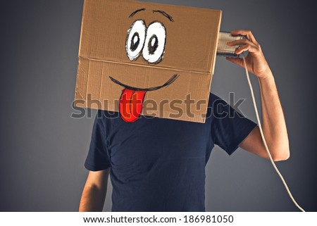 Man with cardboard box on his head using tin can telephone for conversation. Happy emoticon face expression.