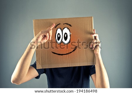 Man with cardboard box on his head with happy face expression just realized something. - stock photo