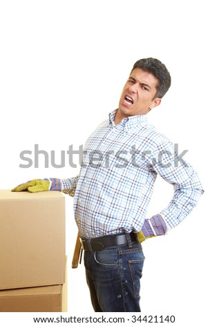 Man with cardboard boxes has pain in his back - stock photo