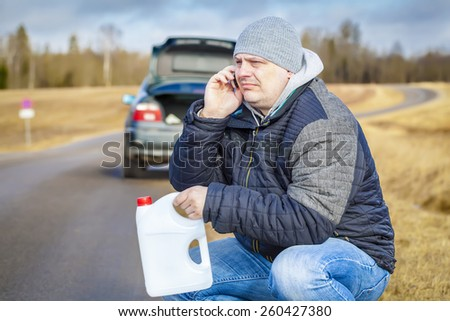Man with cell phone and empty can waiting for help near car  - stock photo