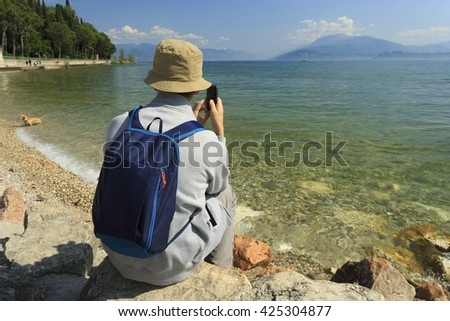 Man with cell phone on the lake