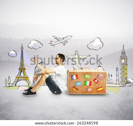 man with cellphone sitting near travel suitcase - stock photo