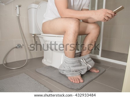 Man with cellphone sitting on the toilet - stock photo