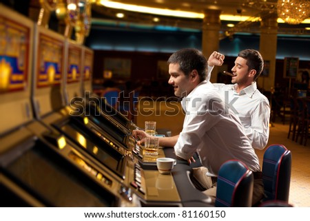 man with cigar in the mouth, sitting by the slot machine, winning - stock photo
