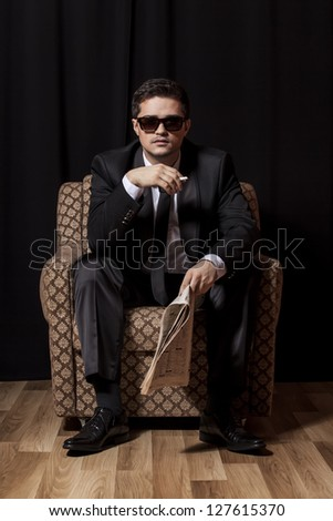 Man with cigarette and newspaper sitting in vintage armchair - stock photo