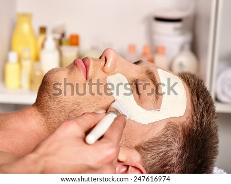 Man with clay facial mask in beauty spa. Male face close up - stock photo