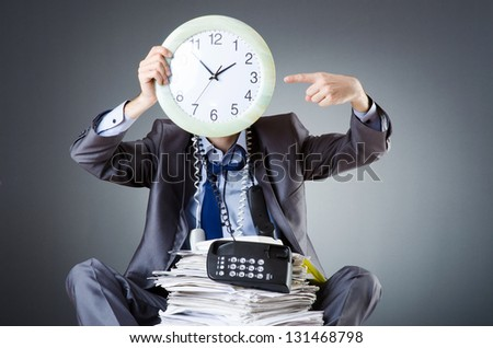 Man with clock and pile of papers - stock photo