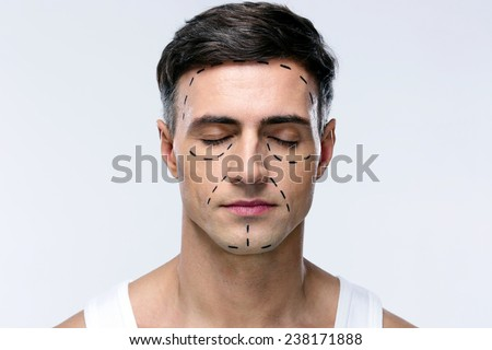 Man with closed eyes and marked with lines for plastic surgery - stock photo