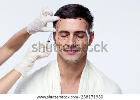 Man with closed eyes at plastic surgery with syringe in his face - stock photo