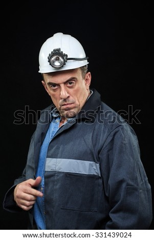 Man with Coal Miner Hat and Safety Clothing points finger