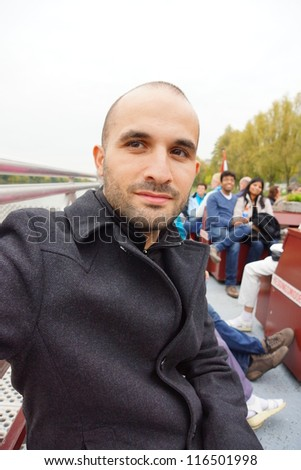 Man with coat sits on a bench - stock photo